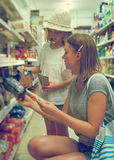 Woman and her daughter choosing snacks. Royalty Free Stock Images