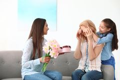 Woman and her daughter congratulating granny. Happy Mother`s Day. Woman and her daughter congratulating granny at home. Happy Mother`s Day royalty free stock photography