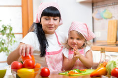 Woman and her daughter are cooking at kitchen. Woman and her kid daughter are cooking at kitchen royalty free stock photos