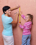 Woman with her daughter doing home repair. Young women with her daughter doing home repair Stock Images