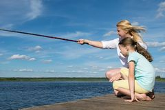 Woman with her daughter is fishing on the pier in sunny weather. Woman with her daughter is  fishing on the pier in sunny weather royalty free stock photo
