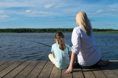 Woman with her daughter is fishing on the pier in sunny weather, rear view. Woman with her daughter is fishing on the pier in sunny weather,  rear view royalty free stock photos