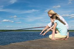 Woman with her daughter is fishing on the pier in sunny weather, side view. Woman with her daughter is  fishing on the pier in sunny weather, side view royalty free stock image