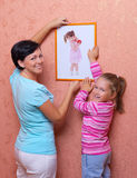 Woman and her daughter hanging up photo. Graphy (of same girl Royalty Free Stock Photo
