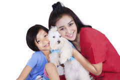 Woman and her daughter hugging maltese dog. Portrait of cheerful young mother and her daughter hugging a maltese dog in the studio, isolated on white background Royalty Free Stock Photography