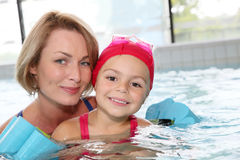 Woman with her daughter learning how to swim. Portrait of women with little girl at the public swimming-pool Stock Photo