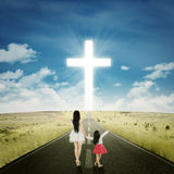 Woman with her daughter looking at a cross Royalty Free Stock Photo