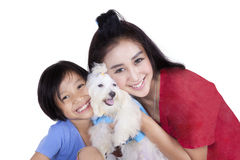 Woman and her daughter with maltese dog. Cheerful young women and her daughter holding a maltese dog in the studio, isolated on white background Royalty Free Stock Photo
