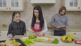 Woman and her daughter prepares salad for dinner. Young housewife stands near the table and preparing dinner for family. Her little daughter helps a woman to stock footage