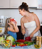 Woman and her daughter preparing dinner. Smiling women and her daughter preparing healthy dinner Stock Photos