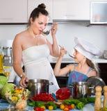 Woman and her daughter preparing veggie food Royalty Free Stock Image