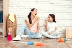 The woman and her daughter rest after tiring the house. They sit on the floor with their backs against the wall and eat. The women and her daughter rest after Royalty Free Stock Photos