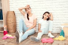 The woman and her daughter rest after tiring the house. They sit on the floor with their backs against the wall and rest. The women and her daughter rest after Royalty Free Stock Image