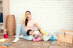 The woman and her daughter rest after tiring the house. They sit on the floor with their backs against the wall and rest. The women and her daughter rest after Royalty Free Stock Images