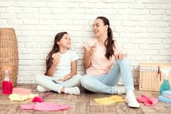 The woman and her daughter rest after tiring the house. They sit on the floor with their backs against the wall and rest. The women and her daughter rest after Royalty Free Stock Photos