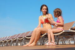 Woman with her daughter sitting on chaise longues Stock Photo