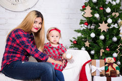 Woman and her daughter sitting in decorated living room with Chr Royalty Free Stock Photo