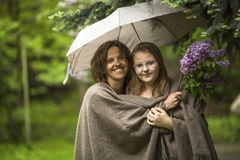 Woman with her daughter standing in the Park under an umbrella. Love. Royalty Free Stock Image