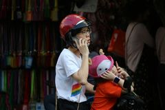 Woman and her daughter stop and park motorcycle for phone at Sampheng trading town stock photos