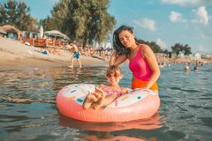 Woman and her daughter swiming on an inflatable donut stock photo