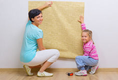 Woman and her daughter with wallpaper roll Stock Photos