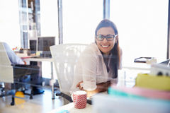 Woman at her desk in an office smiling to camera Royalty Free Stock Photos