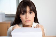 Woman At Her Desk With Pile Of Paperwork. Portrait of overstrained woman at her desk with pile of paperwork Stock Photo