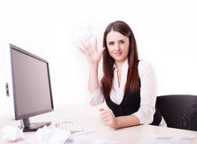Woman at her desk throwing a paper ball Royalty Free Stock Image