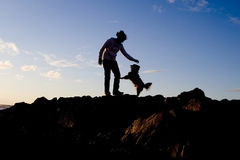 Woman and her dog. A silhouette of a woman and her dog on the beach Stock Images