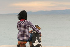 Woman and her dog against the sea watching the sunset. Royalty Free Stock Images