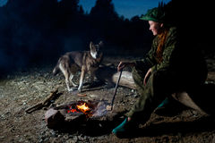 Woman with her dog around campfire at night forest Stock Photo