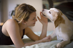 Woman with her dog in the bed at home. A woman with her dog in the bed at home Royalty Free Stock Image