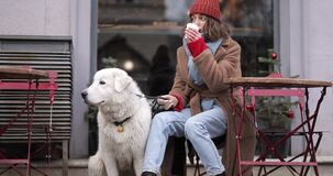 Woman with her dog at the cafe in winter