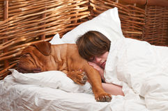 Woman and her dog comfortably sleeping in the bed Stock Images