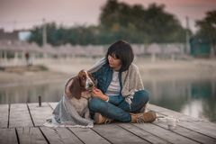 56c4a781b2 Woman with her dog covered with blanket sitting by the river. Portrait of  beautiful young