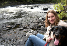 Woman and Her Dog Enjoying Rapids. Young Female sitting by the rapid river with her big dog Stock Photos