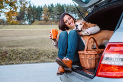 Woman with her dog have a tea time during their autumn auto trav Stock Photo