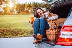 Woman with her dog have a tea time during their autumn auto trav Royalty Free Stock Photo