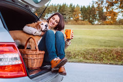 Woman with her dog have a tea time during their autumn auto trav Royalty Free Stock Images