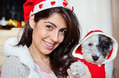 Woman with her dog with red christmas hats Stock Photos