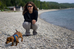 Woman and her dog on a rocky beach Stock Photo