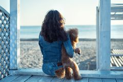 Woman with her dog at sandy sea beach . Royalty Free Stock Photography