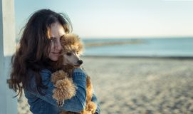 Woman with her dog at sandy sea beach . Royalty Free Stock Image