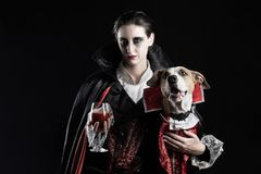 Woman and her dog in similar vampire costumes for halloween. You. Ng female with glass of red drink and her pet puppy dressed up in same dracula costume stock photo