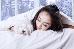 Woman and her dog sleeping on bed Stock Photo