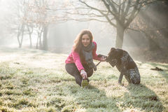 Woman and her dog stretching outdoor. Fitness girl and her pet working out together. Royalty Free Stock Photo