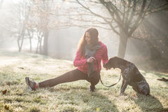 Woman and her dog stretching outdoor. Fitness girl and her pet working out together. Morning scene Royalty Free Stock Images