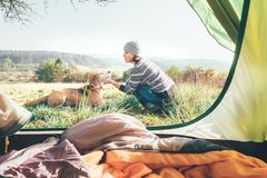 Woman and her dog tender scene near the camping tent. Active lei stock photo