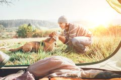 Woman and her dog tender scene near the camping tent. Active leisure, traveling with pet6 simple things concept image royalty free stock images