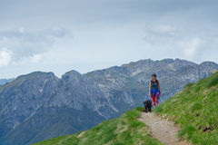Woman with her dog walking on the mountain path Royalty Free Stock Image